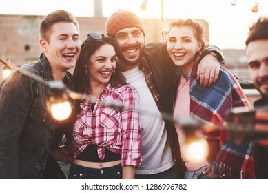 Look at these happy people. Group of young cheerful friends having fun, hug each other and takes selfie on the roof with decorate light bulbs.