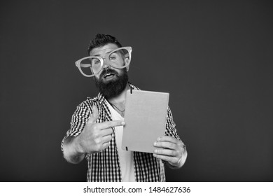 Look at this book. Bearded man in party glasses pointing at lesson book. Study nerd holding book. Book nerd wearing fancy glasses. University male student with lecture notes.