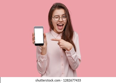 Look at this cell phone! Pleased happy woman blinks eyes, points with index finger at blank screen, shows modern device, dressed in fashionable shirt, isolated over pink background. Technology concept
