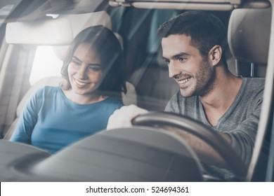 Look at this console! Beautiful young couple sitting at the front seat of the car checking out the side panel