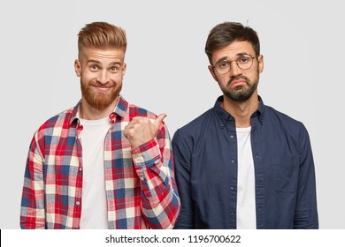 Look at this guy! Ginger bearded young man points with thumb at his fellow who has hesitant expression, suggets to ask him question, dressed in casual clothes, isolated over white background