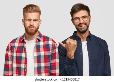 Look at this guy. Smiling unshaven man indicates with thumb at gloomy friend who is dissatisfied with exam results, stand next to each other, dressed in fashionable shirts isolated on white background