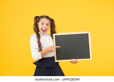 Look at this. Happy girl pointing finger at blackboard on yellow background. Small kid with blank blackboard. Little child holding blackboard for lesson. Blackboard for school advert, copy space.