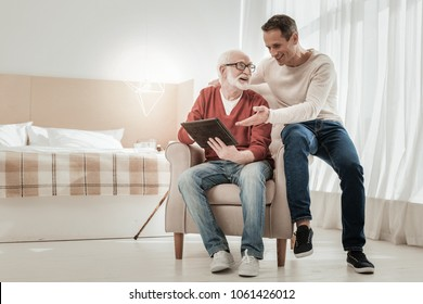 look at this. Happy pleasant satisfied man sitting on the chair near his father smiling and sowing his tablet.
