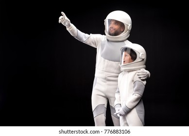 Look at this. Positive cosmonaut father is hugging his son while pointing on something while boy is feeling wonder. They are standing together wearing protective costume. Isolated with copy space