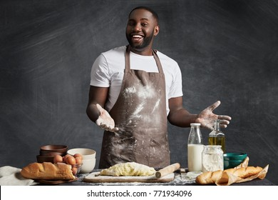 Look at this well made dough! Happy African American male cook or chef boasts of pastry he made by himself, wears dirty apron, has untidy hands in flour, being satisfied with baking results.