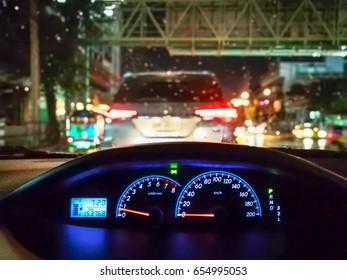 Look through a car wheel with traffic jam. The city at night..Drizzle.