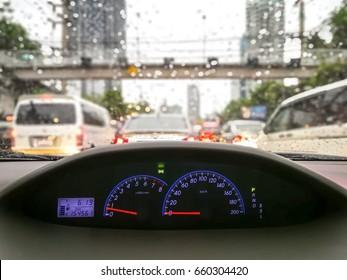 Look through a car wheel with traffic jam and rain drops on car glass