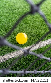 A look through the football net focusing on the yellow ball on artificial green grass.
