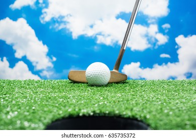 Look through the hole to the golf ball and the putter on fake green grass against cloud and blue sky