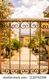 A look through a metal railing at the top of a hill in a small town, in Sicily, Italy.