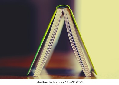 Look through an open book on wooden table upside down