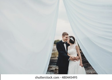 Look through the white cloth at wedding couple hugging on the stones