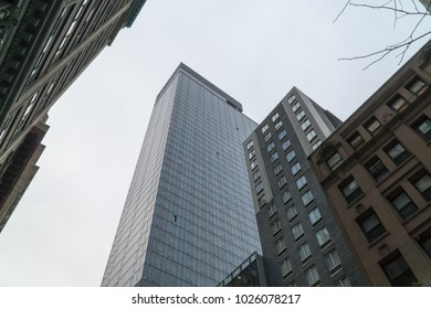 Look up vertical view of New York City style skyscraper office building and smaller apartments below from street level