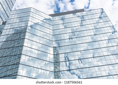 Look up view of modern skyscrapers glass building with cloud reflection