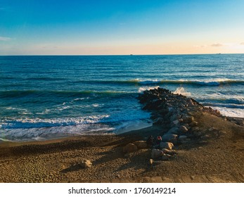 A look at the waves with sea foam, lit by sunlight at sunset, beat against a breakwater with ships on the horizon against a blue sky on a sunny evening.