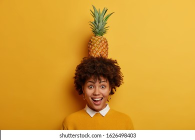 Look what I can do! Cheerful funny woman with Afro hairstyle holds juicy pineapple on head, has fun and laughs, wears yellow jumper and white shirt stands over vivid background. People, fruit concept