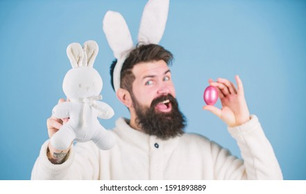 Look what i found. Hipster cute bunny blue background. Easter bunny. My precious. Funny bunny with beard and mustache hold pink egg. Easter symbol concept. Bearded man wear bunny ears. Egg hunt.