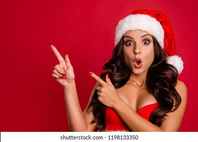 Look what I found! Impressed lady with curly wave hair wow face show forefinger, finger aside on invisible options or alternative make wide open mouth, staring eyes isolated on shine red background