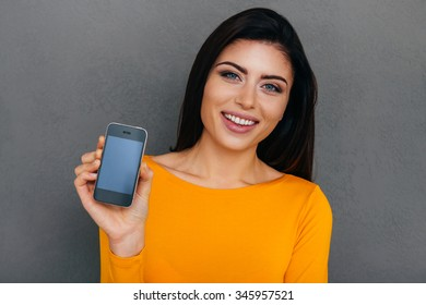 Look what I got! Attractive young woman showing her smart phone and smiling while standing against grey background