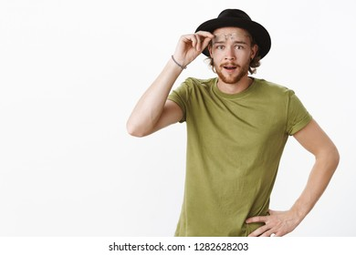 Look what we have here. Portrait of intrigued and interested cute charismatic boyfriend with beard in hat taking off glasses as seeing curious thing looking at camera surprised over gray background