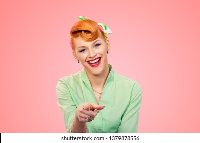Look at you. Beautiful young businesswoman smiling pinup retro vintage hair style girl pointing at you camera laughing, bullying someone while standing against pink background