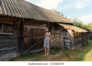 LookBook portrait of a girl in a rustic vintage dress with rakes near a rural barn and cowshed in a courtyard