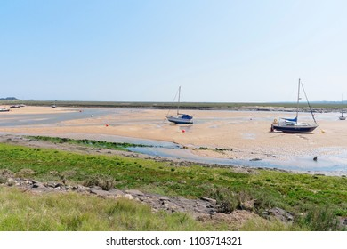 Looking across the estuary at low tide, where yachts are beached on the sand amidst tidal pools, to the salt marshes that stretch to the horizon