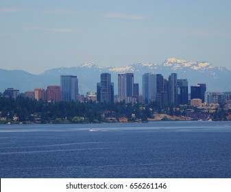 Looking across Lake Washington from Seattle at suburban city of Bellevue, WA & its skyline with snow capped Cascade Mountains directly behind the city buildings on a nice day under a mostly blue sky.