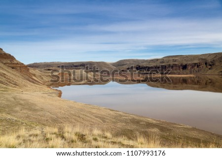 Looking across Lake West on the Palouse River to Marmes Rockshelter historical site on a calm sunny day at Lyons Ferry State Park in Eastern Washington.