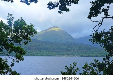 Looking across  Loch Lomond at dawn towards Ben Vorlick with the rising sun kissing its summit, Inversnaid, Stirlingshire, Scotland.