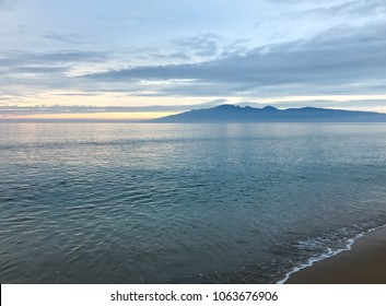Looking across the ocean to the island of Lanai, from a Maui beach, sunset glow on the horizon and reflecting into the ocean.