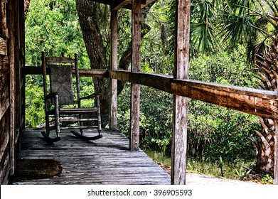 Looking across old wooden porch towards an empty rocking chair with wicker back in tropical estero, florida setting.