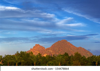 Looking across vivid green trees at Camelback Mountain against a deep blue sky.  Phoenix, Arizona, USA.