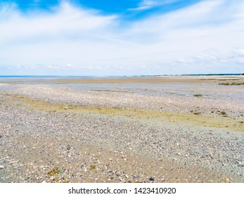 Looking across the wide expanse of beach near the village of Cherrueix, France, at low tide on a hazy spring day.