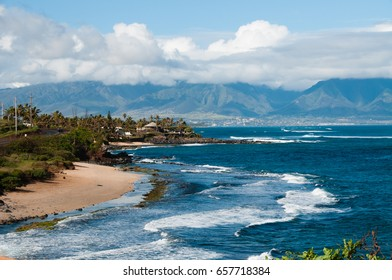 Looking along the coast to town along tropical island with mountains in distance.