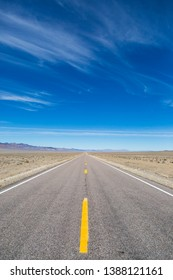 Looking along the Extraterrestrial Highway in Nevada, with a blue sky and wispy clouds overhead