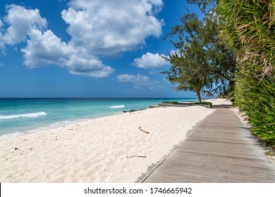 Looking along a wooden boardwalk running alongside a sandy Caribbean beach
