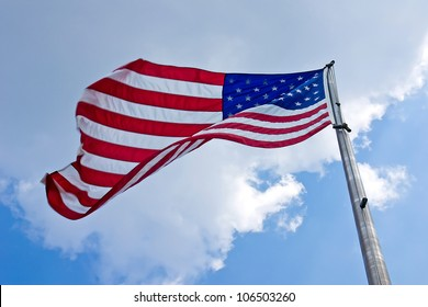 Looking up at an American flag waving on a tall flagpole