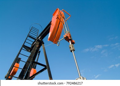 Looking up at an angle at the horsehead of an oil well pumpjack against a blue sky