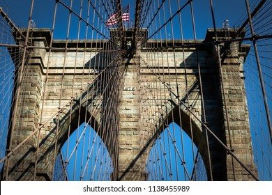 Looking up at the arches and tower of a New York City bridge.