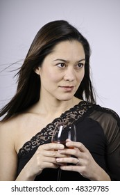Looking away from the camera and holding a glass wine. She is of mixed ethnicity.