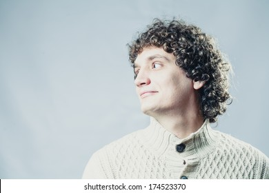 Looking away. Portrait of a young caucasian guy with curly hair