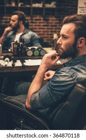 Looking awesome as ever. Side view of handsome young bearded man looking away and keeping hand on chin while sitting in chair at barbershop