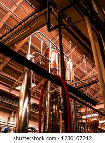 Looking up at a beautiful, copper duel-column pot still in a whiskey distillery.