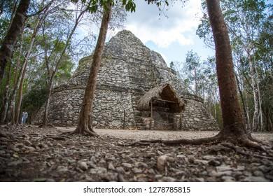 Looking behind the trees at the beautiful Mayan Pyramid in Coba, Mexico