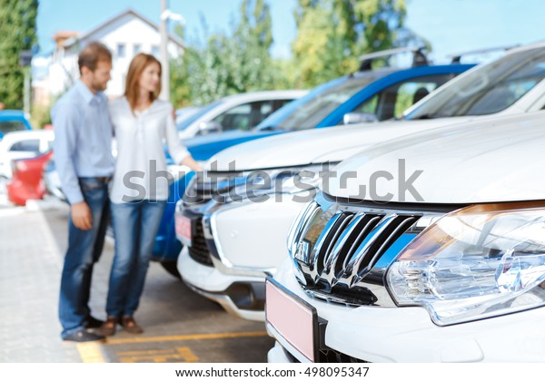 Looking for the best car deal. Selective focus on a car couple choosing a car at the dealership lot on the background