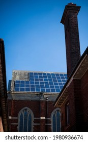 Looking up between buildings at church with solar panels