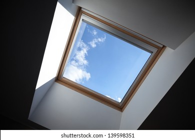 Looking up to the blue cloudy sky through modern square ceiling window