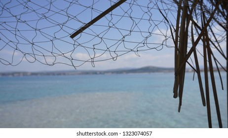 Looking at the blue sea through a straw beach umbrella. Seascape with marsh beach umbrella. Clear sea landscape from a resort in Cesme, Izmır. Summer holiday, relax mode, having fun concept.